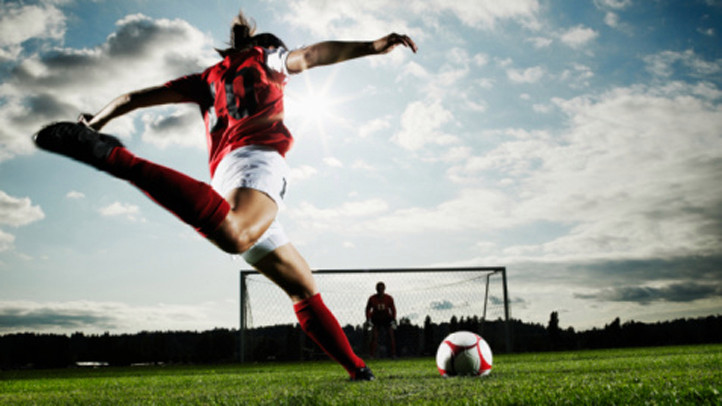 Female soccer player kicking soccer ball toward goal goalkeeper in background